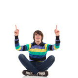 Man sitting with crossed legs on the floor, pointing up. Happy casual man sitting with crossed legs on the floor, pointing up. Full length studio shot isolated Royalty Free Stock Images