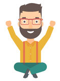 Man sitting with crossed legs and raised hands up. Stock Photography
