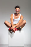 Man sitting on a cube and smiles Stock Image