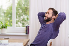 Man sitting daydreaming at the office. Relaxing back in his chair with his hands behind his head staring up into the air Royalty Free Stock Image