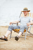 Man sitting in deck chair on beach Royalty Free Stock Photography