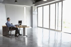 Man Sitting At Desk In Empty Office Royalty Free Stock Image
