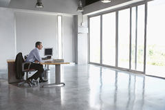 Man Sitting At Desk In Empty Office Royalty Free Stock Photography