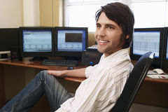Man Sitting At Desk In Front Of Computers Stock Photo