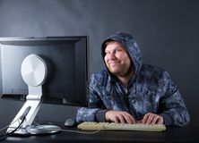 Man sitting at desk looking on computer screen. Fat smiling man sitting at desk looking at computer screen Royalty Free Stock Photography