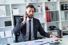 A man is sitting at the desk at the office, talking on the phone and holding a glass of coffee. A bearded man with a business suit is working in a bright office Royalty Free Stock Photos