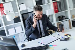 A man is sitting at the desk at the office, talking on the phone and holding a glass of coffee in his hand. A bearded man with a business suit is working in a Royalty Free Stock Images