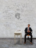 Man sitting on desk and physic formula on wall Royalty Free Stock Photos