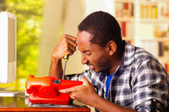 Man sitting by desk repairing handheld sander using screwdriver, upset and annoyed facial expressions while working Stock Photos