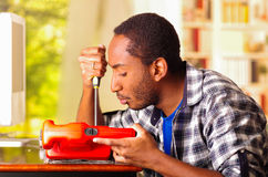 Man sitting by desk repairing handheld sander using screwdriver, upset and annoyed facial expressions while working Royalty Free Stock Photography