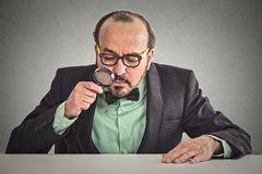 Man sitting at desk skeptically looking through magnifying glass Royalty Free Stock Images