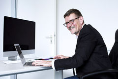 Man sitting at desk and smiling Stock Photo