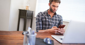Man sitting at desk using cellphone. Tilted image of a young well groomed caucasian entrepreneur busy using his cellphone with both hands while seated at his Royalty Free Stock Image