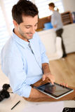 Man sitting on desk and using digital tablet Royalty Free Stock Image