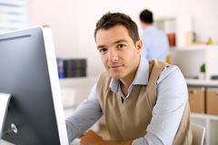 Man sitting at desk and working with computer Royalty Free Stock Image