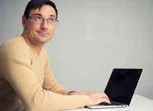 Man sitting at desk, working on laptop computer Royalty Free Stock Photography