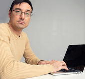 Man sitting at desk, working on laptop computer Stock Photography