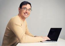 Man sitting at desk, working on laptop computer Stock Image