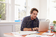 Man Sitting At Desk Working At Laptop In Home Office Stock Image