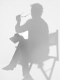 Man sitting on director's chair, silhouette Royalty Free Stock Image