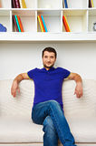 Man sitting on divan and smiling Royalty Free Stock Photography