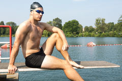 Man sitting on diving board in the sun at lake Royalty Free Stock Photography