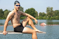 Man sitting on diving board in the sun at lake Stock Image