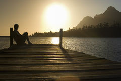 Man Sitting On Dock By Lake Royalty Free Stock Images