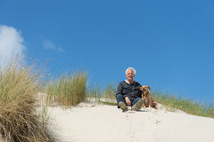 Man sitting with dog in the dunes royalty free stock photography
