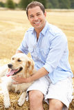 Man Sitting With Dog On Straw Bales In Harvested F Royalty Free Stock Image