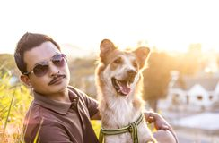 A man sitting with a dog with sun light. stock photo