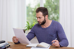 Man sitting doing paperwork in a home office. Attractive bearded man sitting doing paperwork at home or in the office studying a handheld document as he sits at royalty free stock image