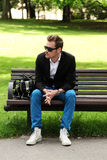 Man sitting down on a bench. In a park wearing jeans and blazer on a sunny summer day Stock Image