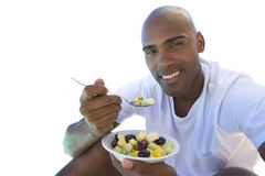 Man sitting down eating bowl of fruit, cut out stock photo