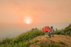 Man sitting and drinking coffee near camping tent. With sunrise or sunset background Royalty Free Stock Image