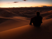 Man sitting on a dune in the desert while watching the sunset. Er Chebbi, Maroc, Africa Royalty Free Stock Photos