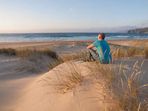 Man sitting in a dune and enjoying the scenery of a beach Royalty Free Stock Images
