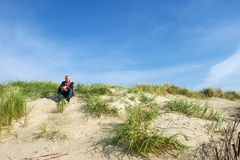 Man is sitting in the dunes royalty free stock image