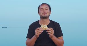 The Man sitting and eat pizza outdoor. Closeup. The Man sitting and eat pizza outdoor. Closeup stock video footage