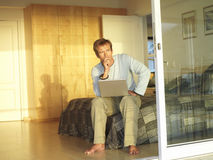 Man sitting on edge of bed, using laptop, hand on chin, thinking, view through open sliding doors Stock Photography