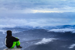 Man sitting on the edge of a cliff,above the clouds Royalty Free Stock Photography