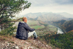 Man sitting on the edge of the cliff above mountaine valley Royalty Free Stock Images