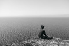 Man sitting on edge of cliff at edge.  Royalty Free Stock Photo