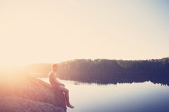 Man sitting on the edge of the cliff near the lake after swimming and looking far away. Young man sitting on the edge of the cliff near the lake after swimming Stock Images
