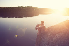 Man sitting on the edge of the cliff near the lake after swimming. Young man sitting on the edge of the cliff near the lake after swimming Royalty Free Stock Photo