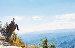 Man sitting on the edge of a cliff overlooking. The mountains below Royalty Free Stock Photography