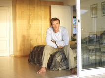 Man sitting on edge of double bed, thinking, view through open sliding doors stock photos