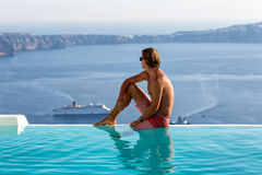 Man sitting on the edge of an infinity pool and enjoying the view Royalty Free Stock Images