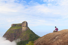 Man sitting on edge of mountain Pedra Bonita, Pedra da Gavea. Man sitting on edge of mountain Pedra Bonita looking at Peak Mountain Pedra da Gavea in clouds blu Royalty Free Stock Images