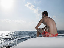 Man Sitting At Edge Of Yacht Looking At Sea Royalty Free Stock Images